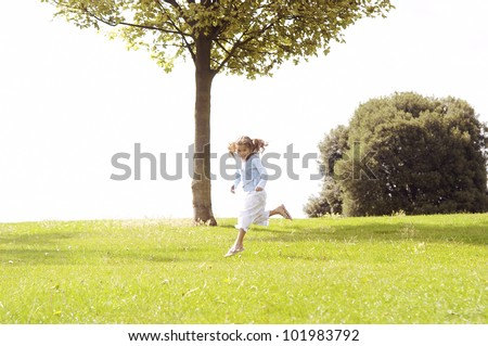 Young girl jumping on a green grass hill. - stock photo