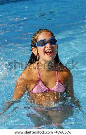 Young girl jumping on a pool