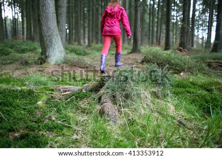Young girl jumping over a puddle in a lush green forest wearing a bright pink coat with rain boots