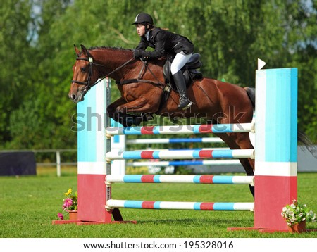 Young girl jumping over obstacle with sorrel horse - stock photo
