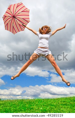 Young girl jumping with an umbrella