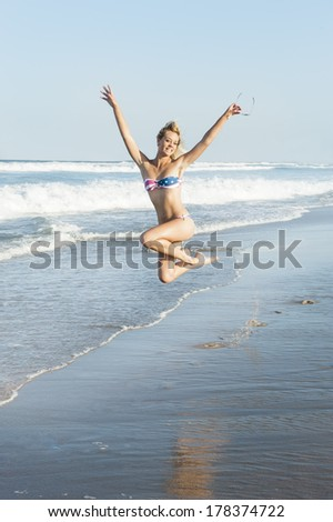 young girl jumping with excitement on beach - stock photo