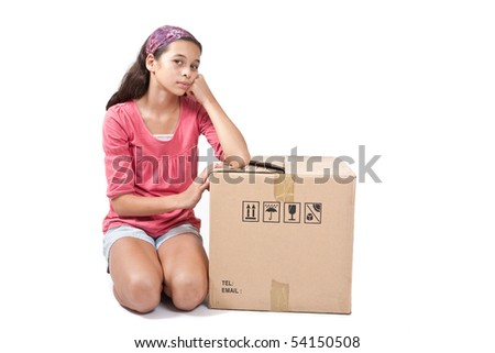 Young girl kneeling by an empty cardboard box. - stock photo