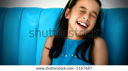 Young girl laughing uncontrollably to a joke made by a friend. - stock photo