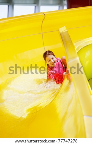 Young girl laughs sliding around the corner of a water slide - stock photo