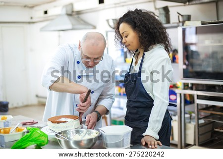 young girl learns to bake cakes with porfessionalnym baker - stock photo