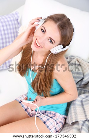Young girl listen to music on home interior background