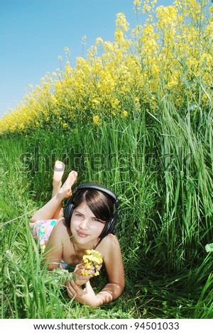 young girl listening music on a springtime field.