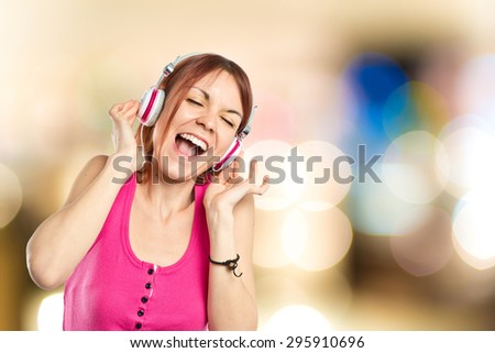 Young girl listening music on unfocused background - stock photo