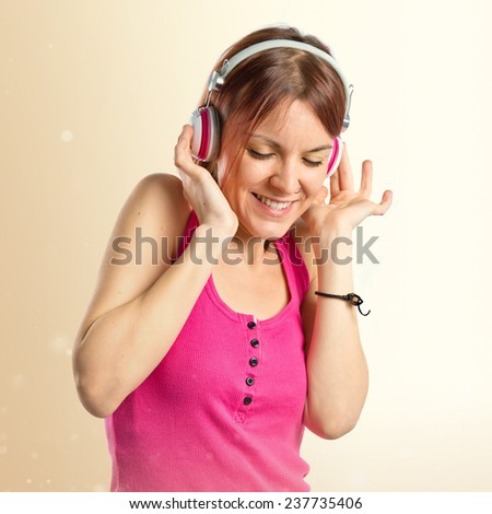 Young girl listening music over ocher background  - stock photo