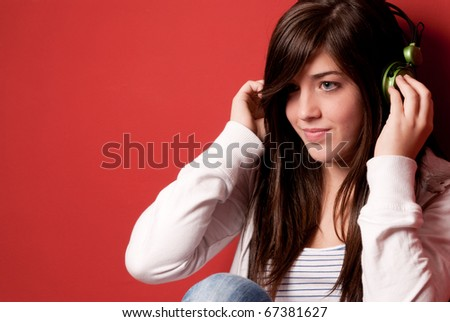 Young girl listening music with headphones on a red wall - stock photo