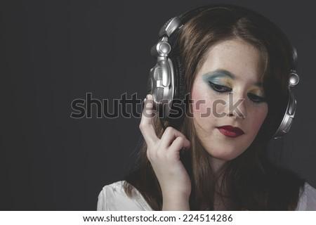 young girl listening music with huge headphones - stock photo