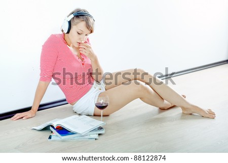 Young girl listening relaxing music with magazines lying on wooden floor - stock photo