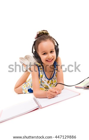 Young girl listening to some music and making a new draw - stock photo