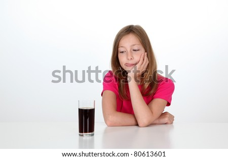 Young girl looking at glass of soft drink - stock photo