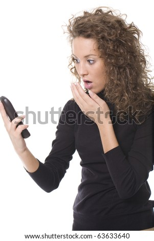 young girl looking at her phone and looking surprised - stock photo