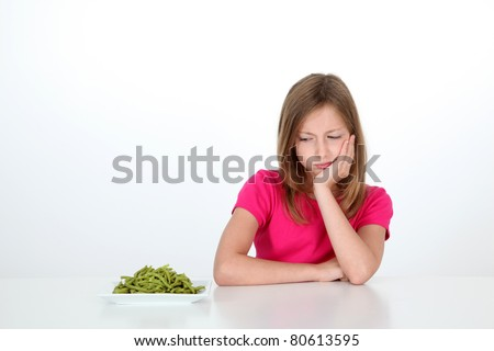 Young girl looking at plate of green beans with disgust - stock photo