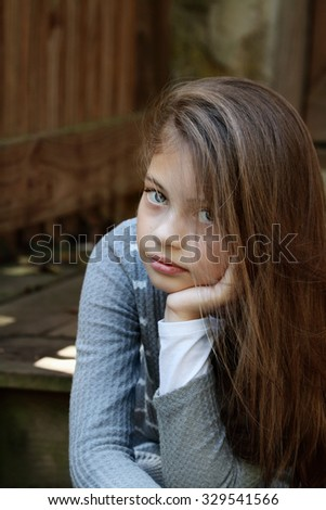 Young girl looking directly into the camera with long flowing hair. Extreme shallow depth of field. - stock photo