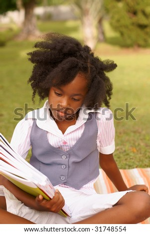 young girl looking down at books in park - stock photo