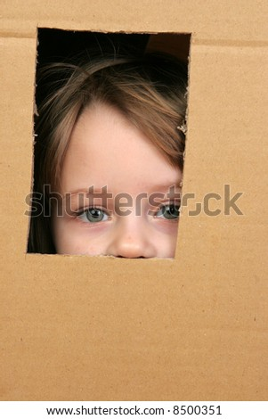 young girl looking from brown carton box