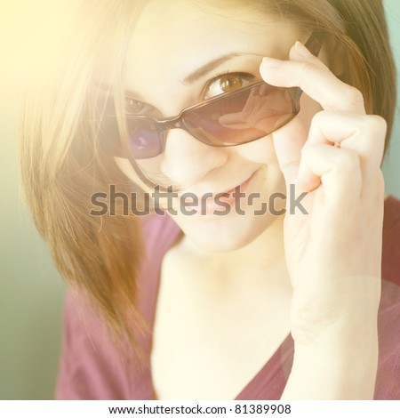 Young girl looking over her sunglasses - stock photo