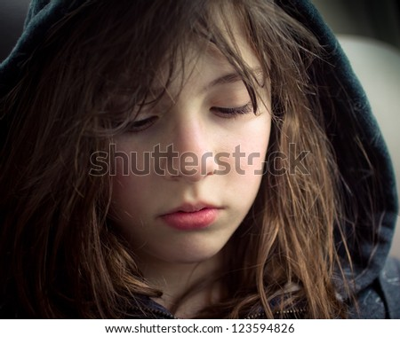 Young girl looking sad and alone - stock photo