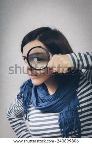 young girl looking through a magnifying glass