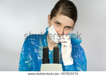 young girl looking through a microscope - stock photo