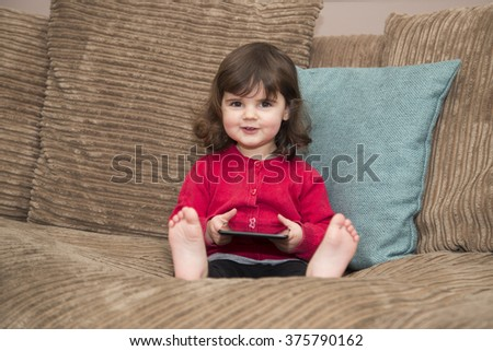Young girl looks up from tablet with a smile - stock photo