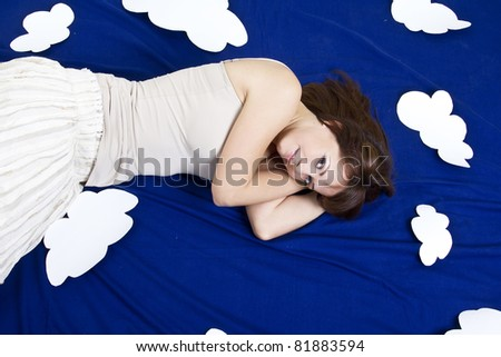 Young girl lying in clouds in studio - stock photo