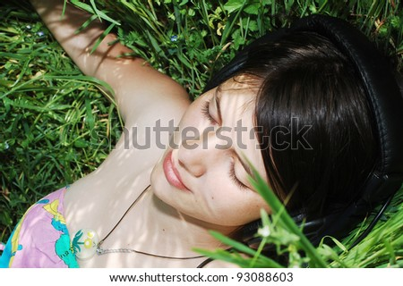 Young girl lying in grass and listening music - stock photo