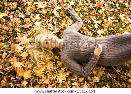 Young girl lying in the Autumn fall leaves - stock photo