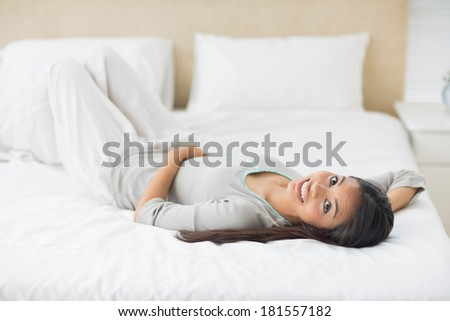 Young girl lying on bed looking at camera in her bedroom at home
