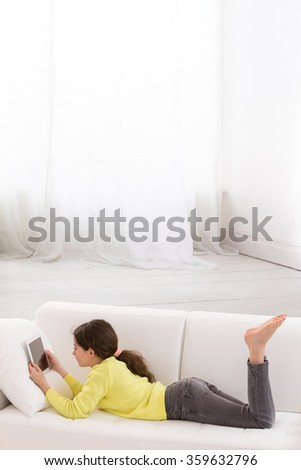 young girl lying on couch with tablet pc computer  - stock photo
