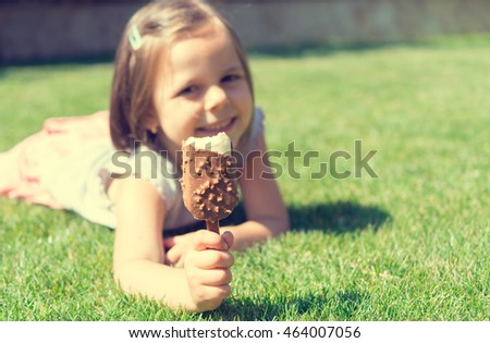 Young girl lying on grass and eating ice cream outdoors