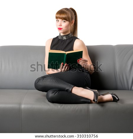 Young girl lying on the couch with a book in her hands - stock photo