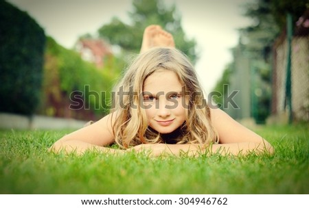 Young girl lying on the grass. - stock photo