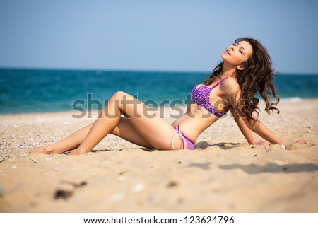 Young girl lying on the sand on the beach - stock photo