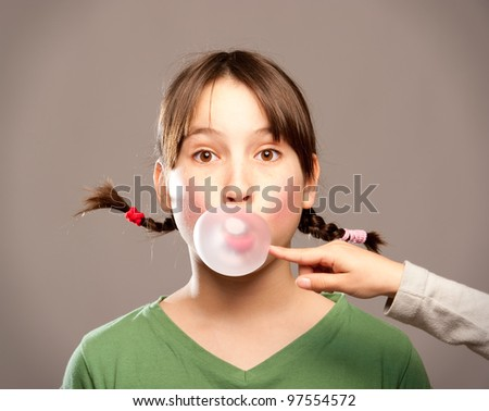 young girl making a bubble from a chewing gum - stock photo