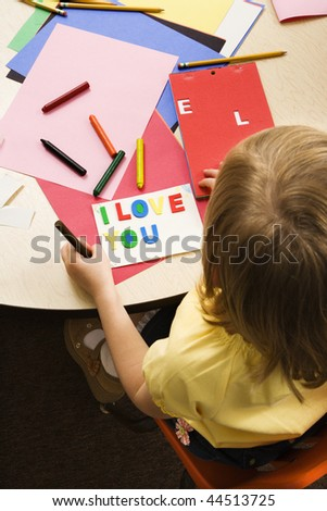 Young girl making card in art class that says I love you. Vertical shot. - stock photo
