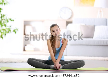 Young girl making fitness exercise indoors - stock photo