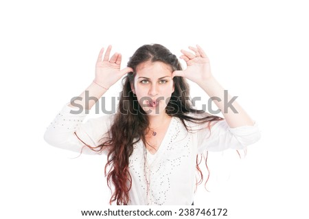 Young girl making funny face using hands and sticking tongue out - stock photo