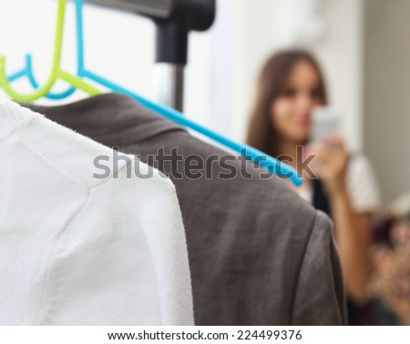 Young girl making photo with mobile camera in shop. Focus on the clothes