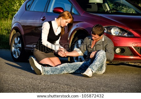 Young girl masures man's pulse on a road. First aid - stock photo