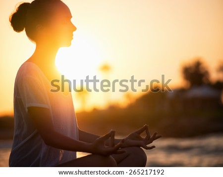 Young girl meditating  in lotus pose - stock photo