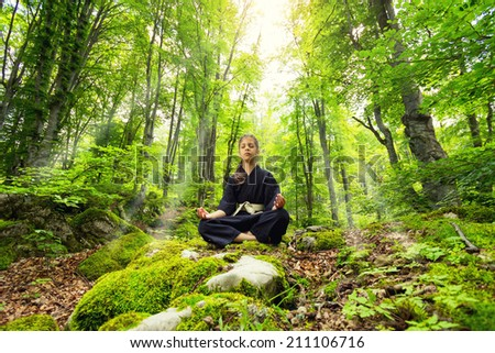 young girl meditating in nature illuminated by sunlight - stock photo