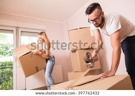 Young girl moving in a new apartment with her boyfriend,standing surrounded with cardboard boxes carries boxes while her boyfriend is packing and taping boxes - stock photo
