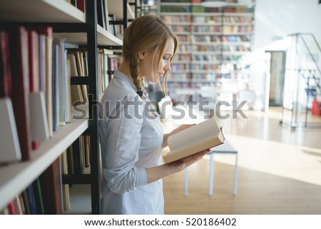 Young girl near the bookshelf