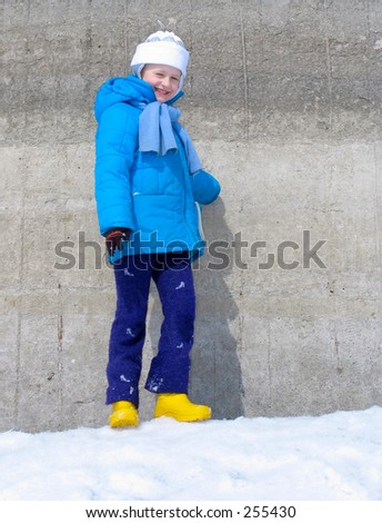 Young girl near the concrete wall
