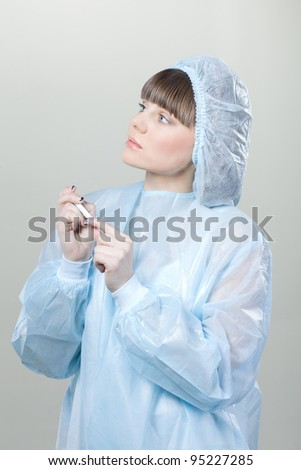 young girl nurse wearing  with a thermometer in hand on white background. nurse, a girl, mask, thermometer, white background - stock photo